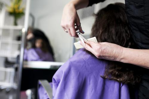 Hairdresser cutting a young girl's hair