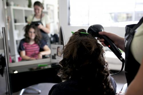Hairdresser styling a young woman's hair