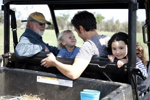 Four people in a farm utility vehicle