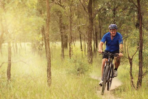 Man riding his pushbike on a dirt track among trees