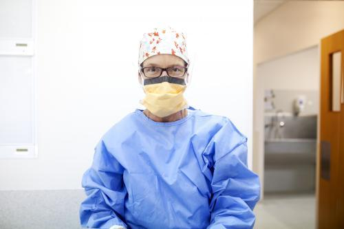Female nurse dressed in protective clothing ready to perform surgery