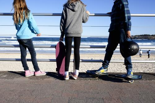 Three kids standing with skateboards looking out at the beach