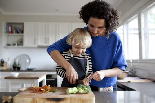 Mum helping young boy cut vegetables