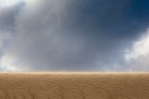 Impressive view up a sand dune towards an imposing cloudy sky