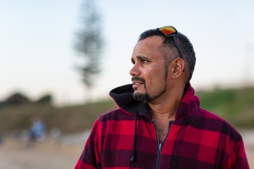 Indigenous man gazing out of frame with sunnies on head
