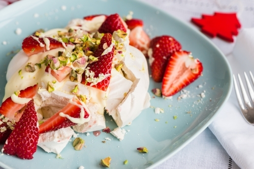 Individual dessert for christmas, a smashed meringue topped with cream, strawberries, pistachio