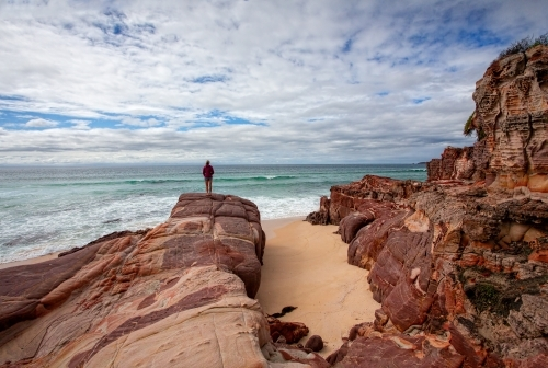 Iron rich red rocks with sandstone offer a dramatic landscape along the coastline beaches Eden