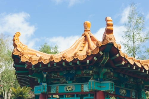 Japanese style golden coloured rotunda roof with trees, blue sky and clouds in the background