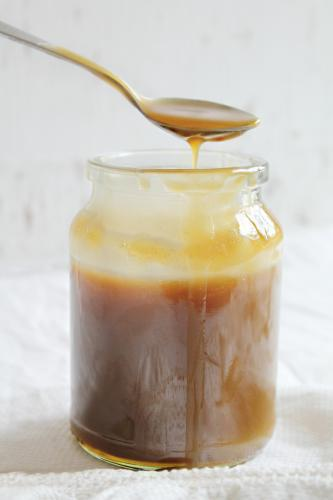 Jar of caramel sauce with spoon dripping