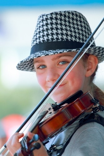 Closeup of a young girl in her early teens busking with a violin.