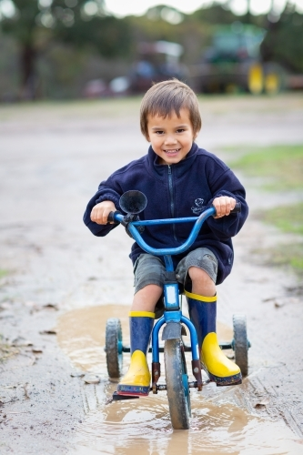 Kid riding a tricycle in puddle