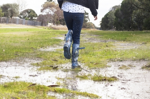 Kid splashing in puddles in gumboots on a rainy winter day.