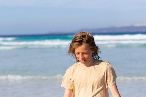 Kid walking with wind in hair at beach