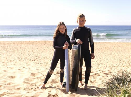 Kids on beach in wetsuits preparing to go body boarding