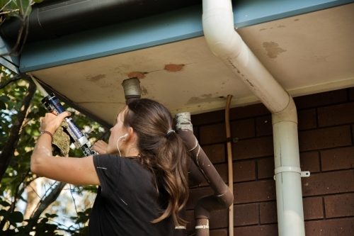 Female tradie fixing eaves in preparation for painting