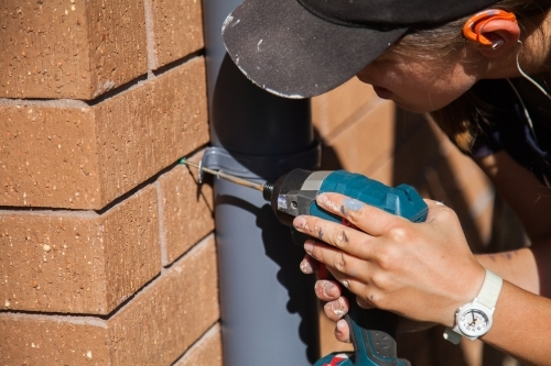 female worker screwing painted downpipe holders onto home