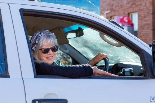 lady wearing sunglasses looking out of car window while driving