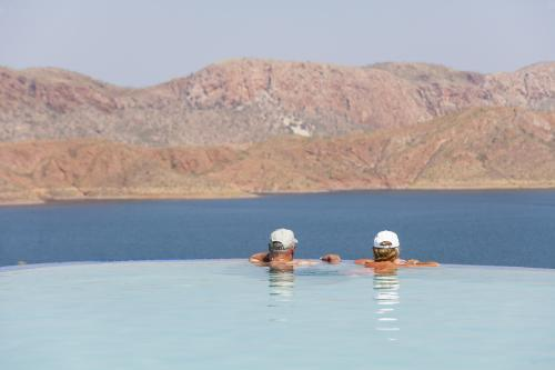 Man and woman in infinity pool overlooking Lake Argyle