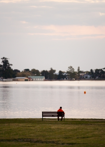 Man sitting on a bench seat at the lakeside