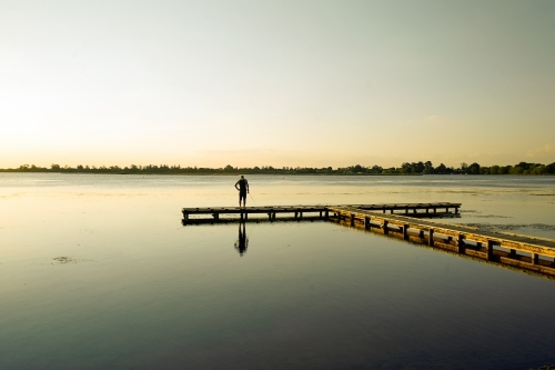 Man fishing at a lake from a jetty