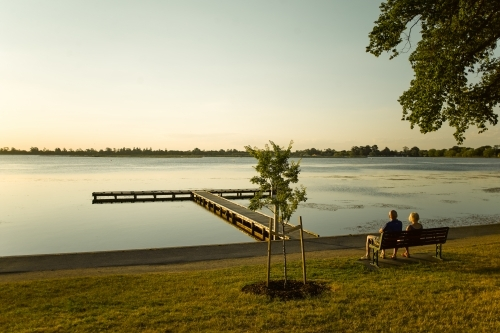 Couple sitting on bench watching the sunset over a lake