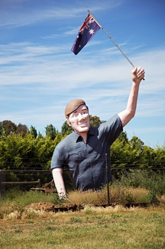 Large sculpture of man holding an Australian flag in a field