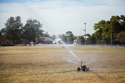 Large sprinkler watering the dry grass on the show ground
