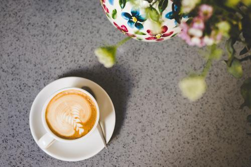 Latte coffee on concrete table with flowers