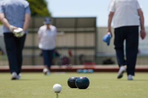 Older woman walking up and down the lawn bowls green