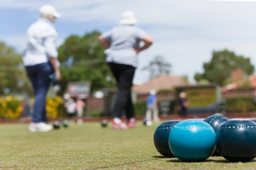 Group of lawn bowls with women in background
