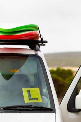 Learner Driver's L plate on vehicle with surfboards on roof