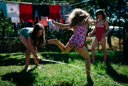 Girls playing under hose, blonde girl jumping over water