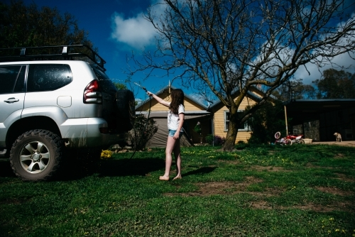 Girl washing car with house in background