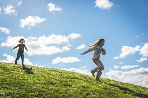 Young girls running down a grassy hill