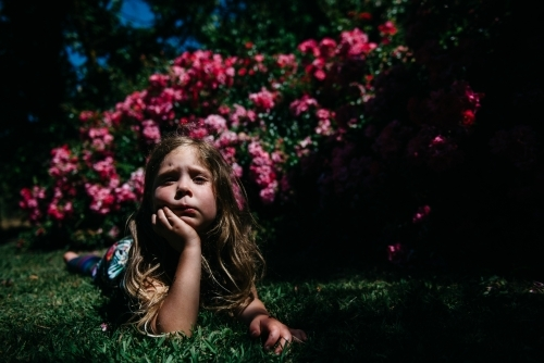 Girl laying in garden, resting her chin in her hand