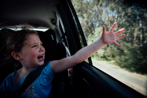 Girl feeling the wind out the car window