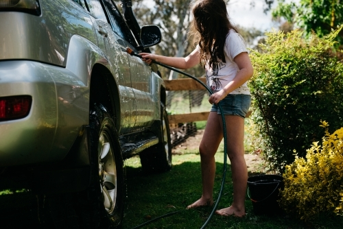 Girl washing a car with a hose