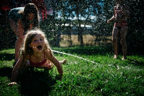 Girls playing under hose, blonde child laughing on ground