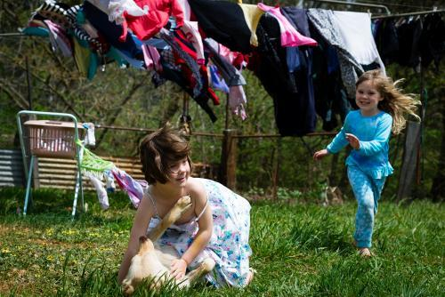 Young girls & their dog play under the clothes line