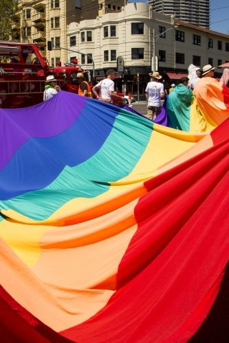 A rainbow flag being carried through a Pride March