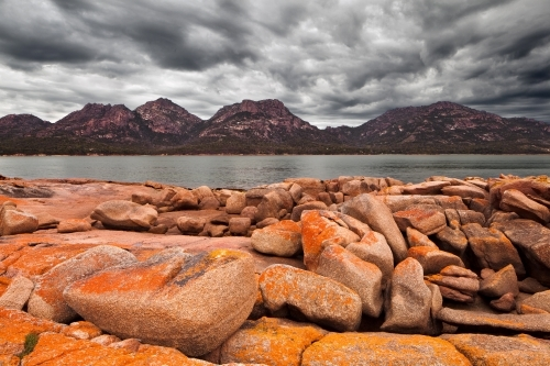 Lichen covered rocks and stormy sky at Coles Bay