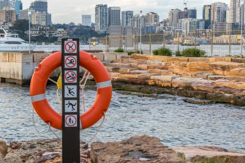 Lifebuoy at city harbour with buildings in distance