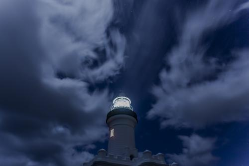 lighthouse at night with cloudy sky behind