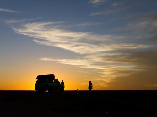 Silhouette against the sunset of a 4WD and people