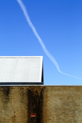 Contrails, a brick wall, and tin roof under a vivid blue sky.