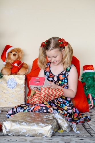 Little blonde girl excitedly looking at a Christmas gift she has just unwrapped