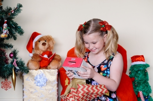 Little blonde girl happily looking at a present she has unwrapped on Christmas day