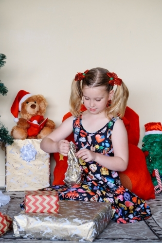 Little blonde girl unwrapping a Christmas present