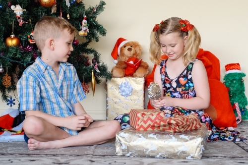 Little boy giving his sister a gift on Christmas day