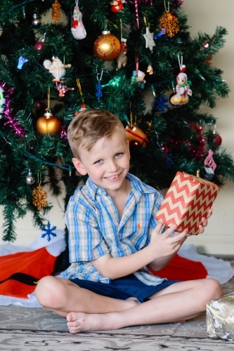 Little boy happily holding a present on Christmas day